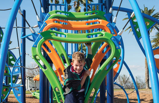 young boy playing on on park equipment